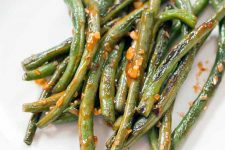 Closeup of sauteed green beans with hot sauce and minced garlic, on a white plate.