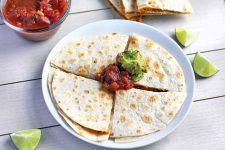 Horizontal overhead image of a quesadilla on a white plate that has been cut into quarters and topped with dollops of guacamole and salsa, on a white surface with a glass dish of sauce, another filled tortilla that has been sliced and stacked, and three wedges of lime.