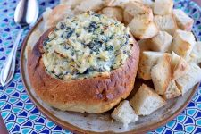 A hollowed boule stuffed with homemade spinach artichoke dip with a golden brown crust on top, next to chunks of bread for serving on a white and terra cotta ceramic plate, with a spoon on a dark and light blue patterned cloth surface.