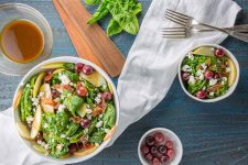 Top down view of a large white bowl of spinach salad with apples, prosciutto, goat cheese crumbles and red grapes, with a smaller bowl of salad to the right, a small white ramekin of pickled grapes, the handles of brown wooden serving utensils, and a few leaves of spinach, with a white cloth and two silver forks on a blue wooden background.