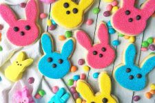 Horizontal image of assorted colored rabbit cut-out cookies on a white table with jelly beans.