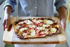A man carries a wooden cutting board loaded with a Strawberry Leek Pizza with Kefir-Soaked Einkorn Crust.