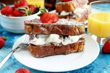 Horizontal image of two French toast slices with a creamy filling in the middle on a white plate.