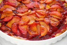 Close up of a Strawberry Peach Tart on Maple Shortbread Cookie Crust in a round, white ceramic baking dish.