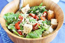 A light brown wooden bowl of panzanella with fresh and roasted vegetables, chunks of bread, and shredded cheese, with a silver stainless steel fork, on a blue cloth background.