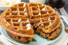 Close up of a two vegan sweet potato waffles with a bite cut out of it sitting on a light blue-green porcelain plate.