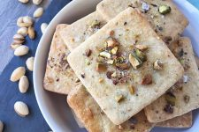 Horizontal image of cookies topped with pistachios in a white bowl.