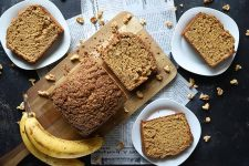 Horizontal image of part of a streusel-topped baked loaf on a cutting board surrounded by slices on white plates, bananas, and walnuts on a dark surface with pieces of paper.