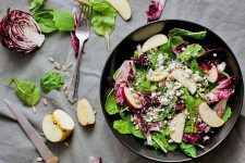 Top-down shot of a black bowl of salad with sliced apple, half a head of radicchio, a fork and serrated knife, and scattered greens on a gray tablecloth.