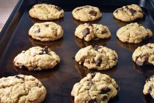 Horizontal closely cropped image of freshly baked chocolate chip cookies arranged in rows on a brown aged metal sheet pan with a short rim, on a beige background.