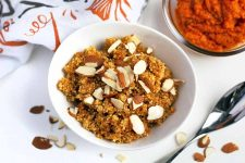 Overhead horizontal image of a white bowl of quinoa breakfast cereal with pumpkin topped with sliced almonds, on a white surface with scattered nuts, an autumn-themed dish towel, a bowl of orange roasted squash puree, and a spoon.