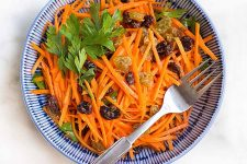 Dig into a bowl of julienned carrot salad with raisins, garlic lemon aioli, and fresh parsley with our recipe. | Foodal.com