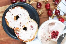 Horizontal image of bagel slices spread with cream cheese surrounded by nuts and whole cherries.