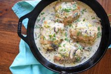 Overhead horizontal image of a cast iron pan of chicken thighs with the skin on, cooked in a cream sauce with leeks and mushrooms, on a wood surface with a gathered light blue cloth dish towel.