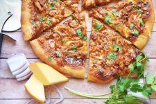 Horizontal overhead closely cropped image of a homemade barbecue chicken pizza that has been cut into triangular slices, on a wood table with a pizza cutting wheel, chunks of gouda cheese, chopped red onion, and sprigs of fresh cilantro.