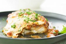 Front view of homemade chicken Parmesan bake sitting on a cast iron pan.