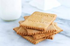 A small stack of five homemade graham crackers with scored edges and rows of holes in the top of each, beside a glass bottle of milk and a white ceramic cake stand, on a gray and white marble background.