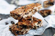 Three stacked homemade granola bars stacked in the foreground with more in soft focus in the background, on pieces of crumpled white parchment paper, on a dark brown wood surface with scattered oats and chocolate chips.