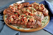 A platter of grilled steak with crumbled feta and tomato salsa, on a gray surface with silverware and two gray-blue cloth napkins.