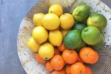A beautiful bowl of assorted lemons, limes, and oranges.