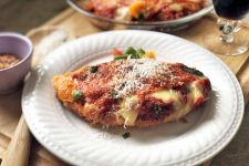 Horizontal oblique overhead image of chicken parmesan with pepperoni on a white plate, garnished with grated parmesan cheese, on a wood surface with a glass of wine, a pie plate containing more of the dish, a small white cup of red pepper flakes, and a wooden cooking spoon.
