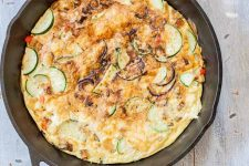 Top-down shot of a potato and zucchini egg frittata in a cast iron pan, golden brown on top, on a distressed wood background.