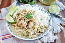 A plate of shredded chicken with a light green sauce and cannellini beans on a bed of white rice, on a white cloth with orange, pink, and purple stripes, with cut limes, a glass bowl of salsa verde, and fresh cilantro, on a brown wood surface.