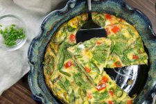 Crustless vegetable quiche with asparagus, spinach, and red bell pepper in a blue-green ceramic scalloped pie dish with a triangle slice cut out and resting on top of a pie server on top of the quiche, on a brown wood table topped with a white cloth, with a small dish of chopped chives.