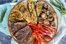 Horizontal top-down image of a platter with assorted grilled summer produce.