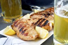 Horizontal image of four grilled chicken breasts on a white serving platter with wedges of lemon, with two mugs of beer to the right and left, and a white cloth with blue stripes in the foreground, on a gray slate surface.
