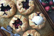 Horizontal image of a baking tray with individual berry pastries.