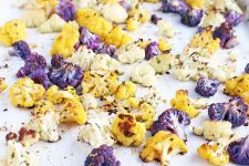 Closeup of orange, white, and purple roasted cauliflower florets coated with chopped fresh herbs, on a white parchment paper background.