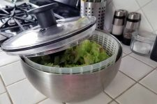 A stainless, acrylic, and black plastic salad spinner with an open top to show the dried lettuce inside, on a white tile kitchen countertop with salt and pepper grinders and a salt cellar in the background.