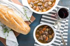 Top-down image of a loaf of French bread on a brown wooden cutting board topped with a white dish towel and a sprig of thyme, to the left of a white bowl and a white ceramic serving bowl of beef bourguignon, on a folded gray and white striped towel with a glass of red wine on top, on a blue wooden surface.