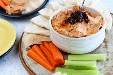 A small white bowl of sun-dried tomato hummus topped with sun-dried tomatoes, on a platter surrounded by triangles of pita bread, carrot sticks, and celery sticks, on a gray table beside a blue and yellow plate, and another dark blue plate of hummus and vegetables.