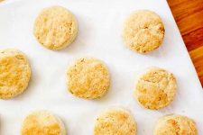 Overhead shot of golden brown homemade biscuits arranged in rows on white parchment paper, on a brown wood surface.