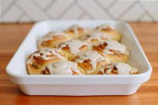 Horizontal image of a white tray with freshly baked cinnamon rolls with glaze.