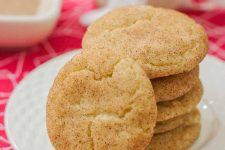 Closeup of a stack of cookies with one leaning against the stack in the foreground, on a white plate, with a square dish in the background, on a red tablecloth.