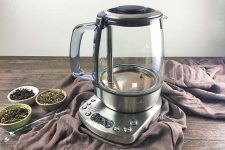Horizontal image of a tea kettle and power base on a brown towel on a brown wooden table.
