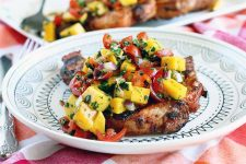 Caramelized grilled bone-in porkchop on a white dinner plate with a black geometric design, topped with mango, cilantro, and tomato salsa, on a red, orange, and white checkered tablecloth with silverware and another plate in the background.