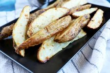 Horizontal image of a black platter with skin-on baked wedges of seasoned potatoes on top of a striped towel.