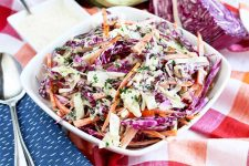 A square bowl of coleslaw is on a table topped with a red and white checkered cloth, with a stainless steel serving spoon atop a folded blue cloth napkin with white dots, and a smaller square dish of a white mayonnaise sauce, with half of a purple cabbage at the top right of the frame.