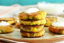 A small stack of four yellow corn and jalapeño arepas, fried until golden brown, topped with a dollop of sour cream and a pinch of chopped cilantro, with more of the corn cakes, a small dish of chopped herbs, and a bowl of sour cream on a tan plate and a tan cloth in the background, against a blue-green wall.