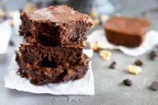 Horizontal image of a stack of three brownies on top of a piece of parchment paper on a gray surface scattered with nuts and chocolate chips.