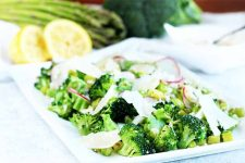 A white, square plate of sautéed asparagus and broccoli with thinly sliced radishes and parmesan cheese, with whole vegetables and a cut lemon in soft focus in the background.