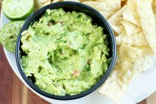 Top-down shot of a black bowl of green guacamole with tortilla chips and a lime cut in half with one half that has been juiced already, on a brown wood background.