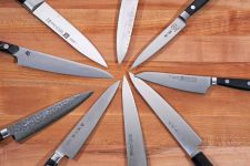 Top down view of 9 different kitchen utility and petty knives with their tips all pointed to one point and organized in a circle.