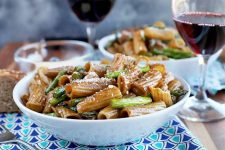 Horizontal head-on image of two white bowls of pasta with asparagus and a brown sauce, with a small glass bowl of grated Parmesan and two glasses of red wine, on a dark and light blue cloth with a triangular pattern on a brown table, with a mottled gray background.