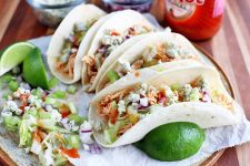 Four chicken tacos with hot sauce, blue cheese, lettuce, onion, celery, and lime, on a marble round serving platter with a bottle of hot sauce and small dishes of chopped vegetables, on a wood surface.