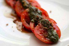 Vegan Basil Walnut Pesto spread up top a row of sliced tomatoes.
